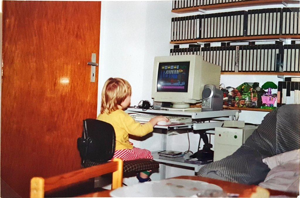 Sabine sitzt als Kind vor einem alten PC
