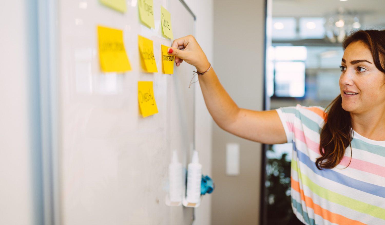 Eine Frau klebt Notizen ans Whiteboard