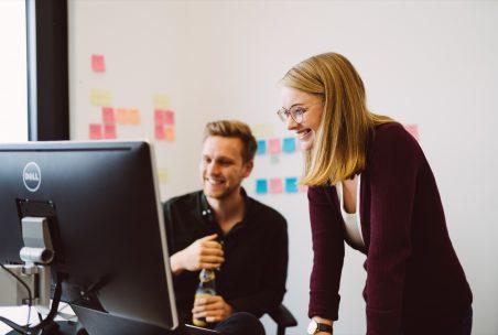 Eine Frau und ein Mann schauen auf einen Bildschirm