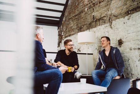 Drei Männer sitzen im Kreis und unterhalten sich