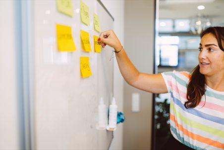 Eine Frau klebt Notizzettel an ein Whiteboard