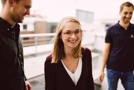 Eine Frau lacht in die Kamera zwei Männer stehen im Hintergrund