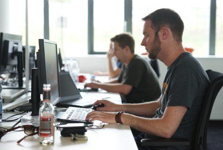 Drei Männer sitzen am Schreibtisch und unterhalten sich