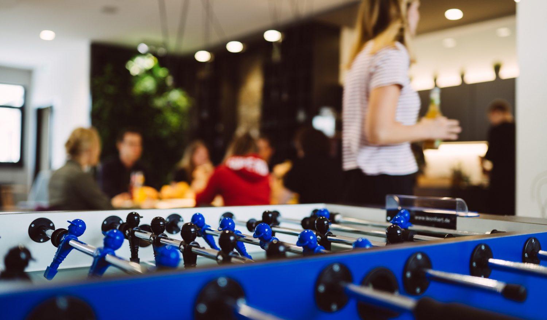 Im Vordergrund ein Tischkicker dahinter sitzen Menschen am Tisch
