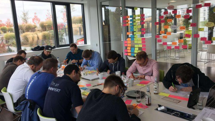 Eine Gruppe von Menschen arbeitet konzentriert am Tisch.