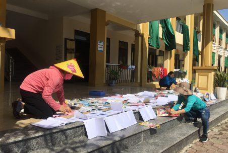 Kinder trocknen Hefte in der Sonne