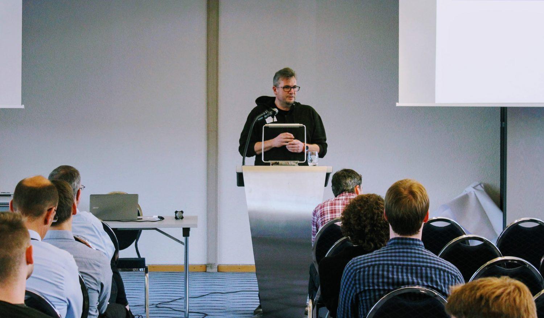 Ein Mann steht an einem Rednerpult vor Publikum