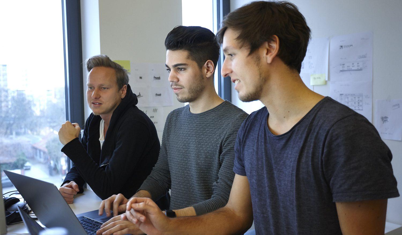 Drei Männer blicken auf einen Bildschirm