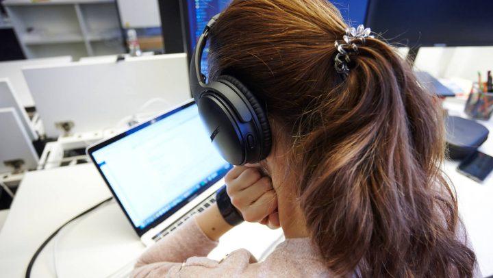 Frau mit Kopfhörer am Laptop
