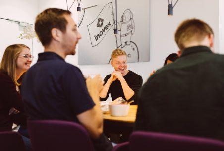 Mehrere Mitarbeiter:innen gemeinsam am Tisch in unserem Hamburger Office