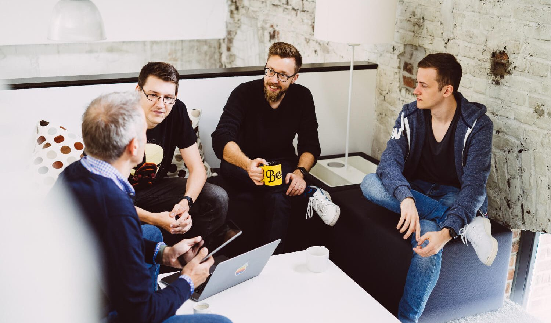 Eine Gruppe von Kollegen sitzt in einer Sitzecke und unterhält sich.