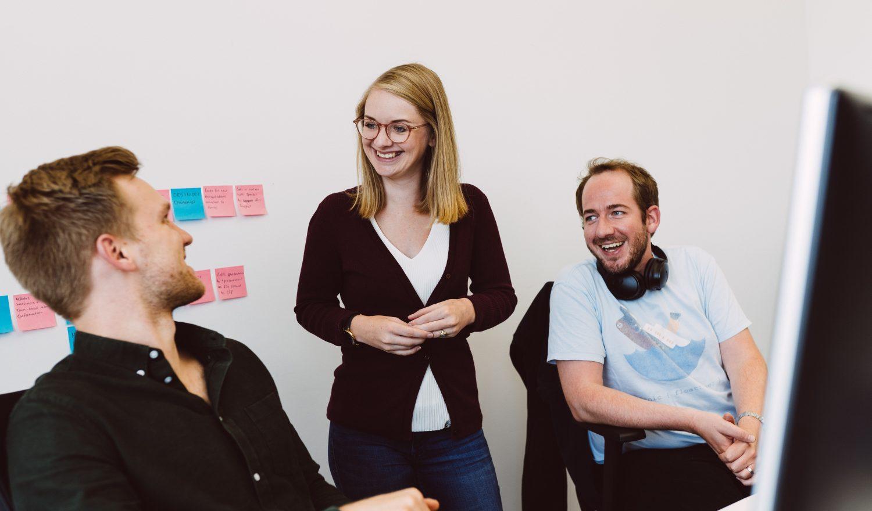 Drei Mitarbeiter:innen unterhalten sich