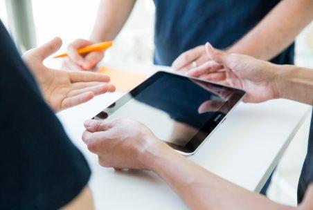 Drei Menschen betrachten ein Tablet mit Service Meister Dashboard