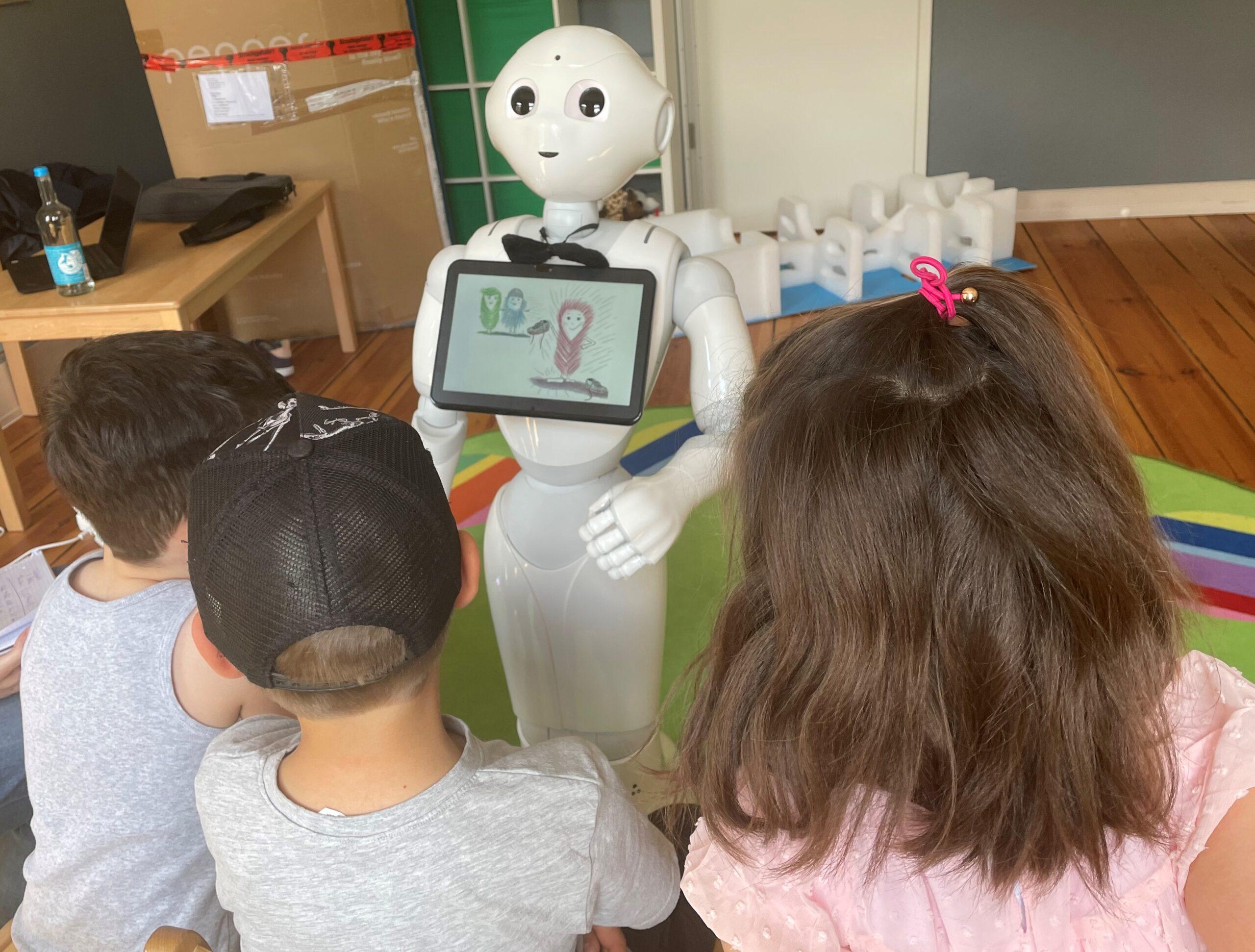 drei Kinder sitzen vor Pepper und hören zu wie der Roboter eine Geschichte erzählt