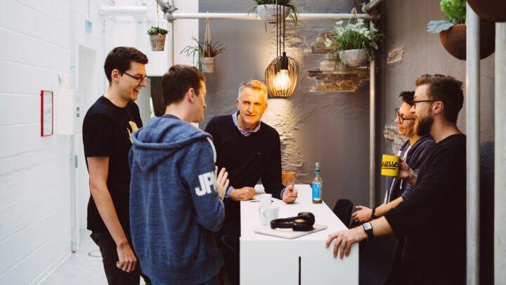Fünf Kollegen stehen zusammen an einem Tisch und unterhalten sich.